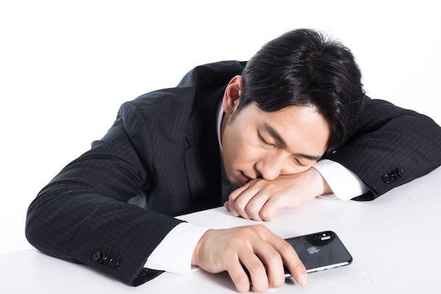 スマホを持って寝る男性