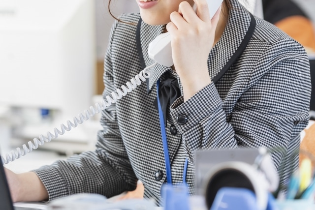 笑顔で電話に出る女性