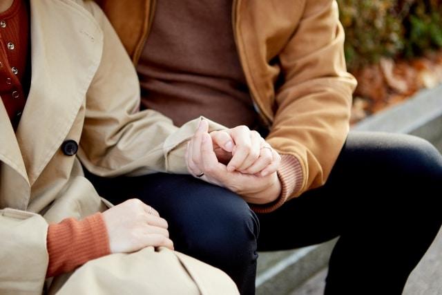 女性の手を握る男性